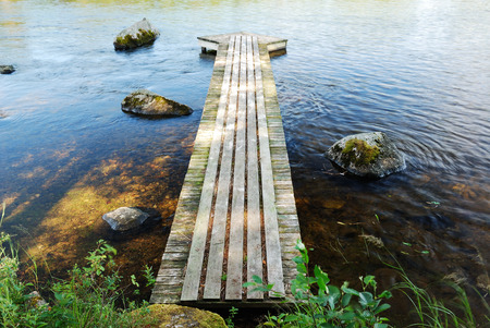 recedes: A planked platform recedes into the transparent lake  It is made in the form of an arrow  Stock Photo