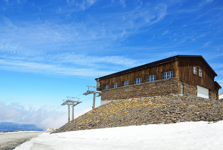 thawing: Andalusian Sierra Nevada is photographed at the Pradollano ski resort in spring  There is the downhll with a snowfield thawing, an idle ski lift and an empty refuge   Editorial
