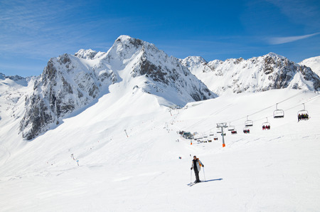 There are snow slopes of mountains from the pass of Tourmalet in the winter Pyrenees  Many skiers are being transported with a gondola lift