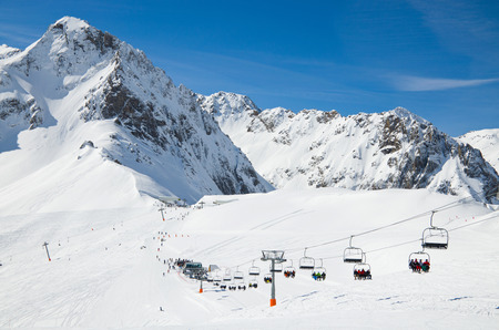 There are snow slopes of mountains from the pass of Tourmalet in the winter Pyrenees  Persons are being transported with a ski lift