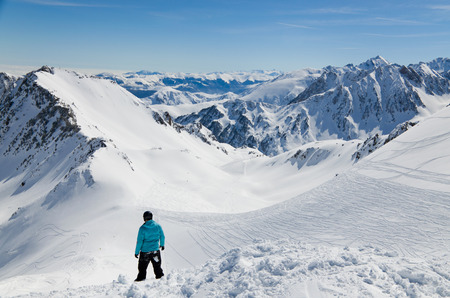 There are snow slopes of mountains from the pass of Tourmalet in the winter Pyrenees  A skier is standing above the downhill  photo
