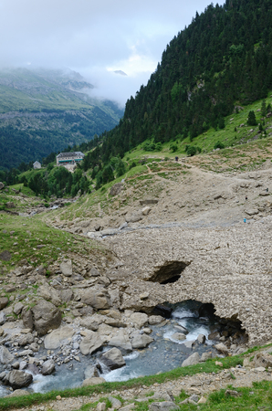 thawing: Summer mountains are photographed in the neighborhood of the cirque of Gavarnie  A glacier is melting  The stream is running from under