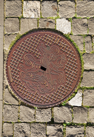 coining: Metal sewer hatch is on the stone block pavement  It is decorated with coining picture