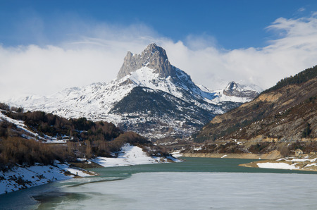 The recognizable mountain  Pena Foratata  is towering above the artificial lake  Embalse de Lanuza  in the Spanish Pyrenees   photo