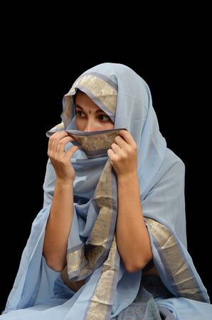 furtively: Caucasian young woman is wearing a traditional dress of women in the Indian Subcontinent  She is hiding her face and looking by stealth  Stock Photo