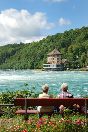 A senior couple is sitting on the bench and seeing the sights of Rhine Falls  There are also viewing platforms built on both sides of the Rhine