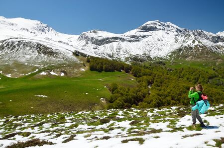 A preteen girl is standing and photographing on the spring slope covered with snow in Pyrenees