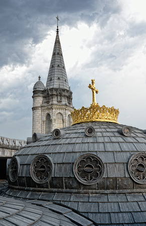 surmounted: Dome of the Rosary basilica is surmounted with the gilded crown and the cross. They are photographed against the overcast sky in Lourdes.