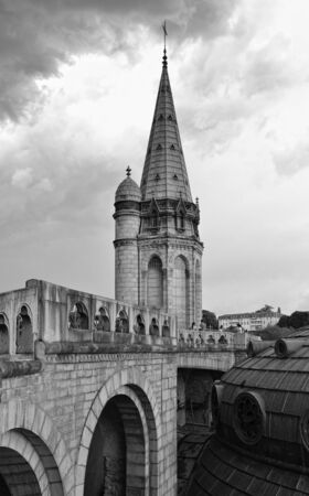 surmounted: Dome of the Rosary basilica is surmounted with the gilded crown and the cross  They are photographed against the overcast sky in Lourdes