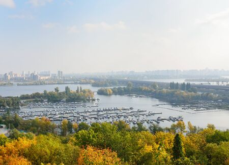 dniper: There are a lot of small piers with various boats, motorboats and islets in the wide river  Dniper is photographed from the right site of Kyiv