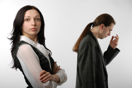 disillusioned: A young woman is standing in close pose and looking at the camera  In the background there is a disappointed man