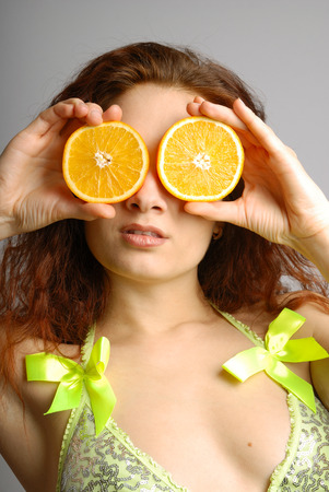 closing eyes: Young woman closing eyes with slices of orange