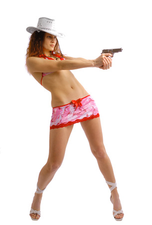 Sexy woman is aiming a pistol with both hands. She is wearing a white hat, a short skirt and a top decorated red bowls   photo