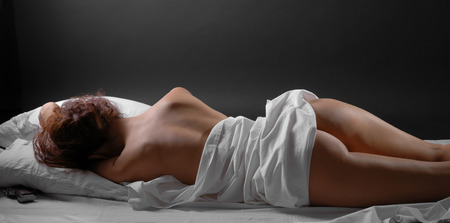 A nude young woman is lying on the white bed-clothes  Her handgun is hidden under the pillow  photo