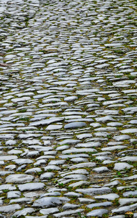 The medieval cobblestone road is made of various pebbles and different shingles  It is photographed close-up and with perspective