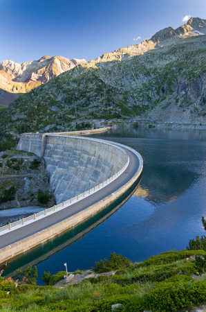 mirror on the water: The concrete dam has formed an artificial lake between mountains.  The blue sky is reflected in the mirror water surface at the sunset