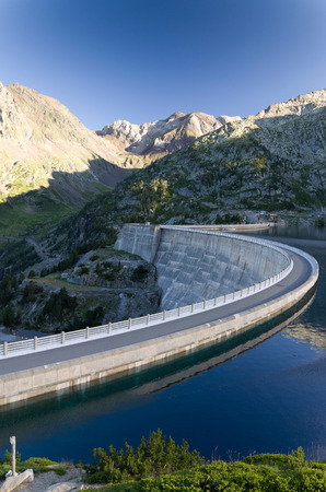 mirror on the water: The concrete dam has formed an artificial lake between mountains  The blue sky is reflected in the mirror water surface at the sunset