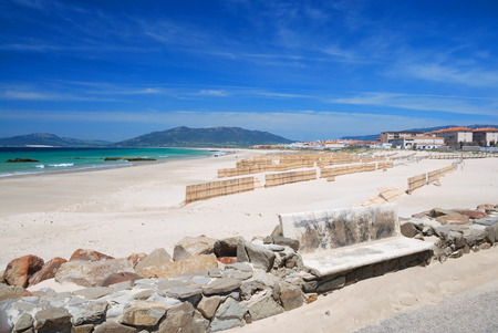 gusty: Windy sand beach with wooden sand-fences against the blue sky of Tarifa and Mediterranean sea, remote settlement and mountains in the background  Stock Photo