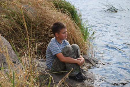 narrowly: Pre-teen boy sits on the rock near the river  He looks narrowly into the distance at windy day