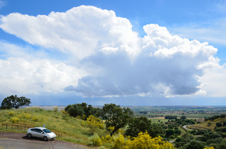 The blue sky with a lot of clouds is photographed above the green spring plain  photo