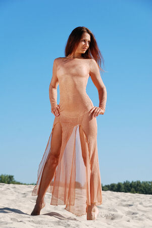 transparent dress: Young woman is standing on the sand beach  She is wearing a transparent long dress  She is acquiring a tan in the sun
