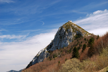 inaccessible: The inaccessible Cathar castle Montsegur is on the peak in the spring mountains  Ruins of towers and surrounding walls are blasted a long time ago