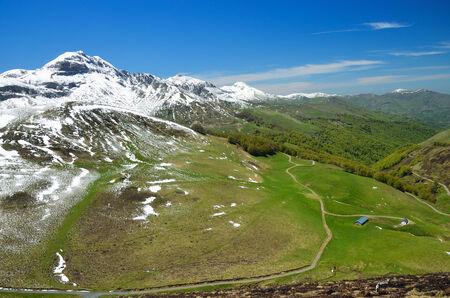 春の山脈ピレネー山脈の雪で覆われた緑の斜面に田舎道をねじる