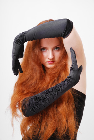 A red-haired witch is looking fixedly at the camera  Her hands frame her beautiful face  The young woman is wearing a black dress and long gloves
