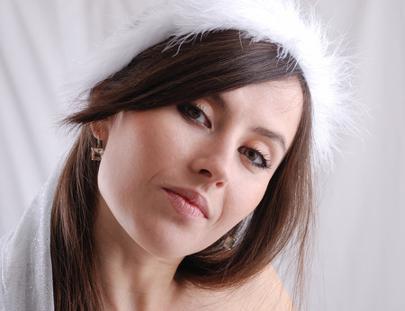 head tilted: Portrait of the dark-haired girl in the cap trimmed with down, suspicious look, head tilted sideways Stock Photo