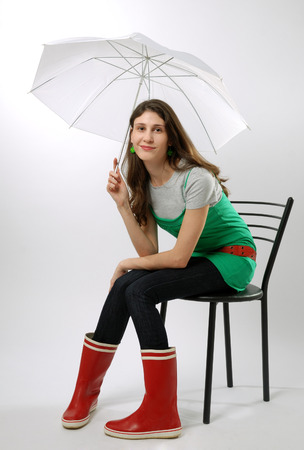 Teenage girl is sitting on the chair  She is holding an umbrella  She is wearing the red boots and green dress