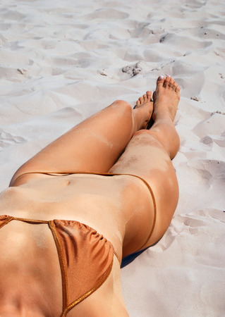 sunburned: Young woman is lying on the sand  She is wearing a brown bikini  She is acquiring a tan in the sun  We are looking part of her sunburned body  The photo is made with very big depth of field