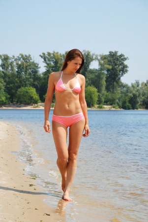 The young woman is walking barefoot along the river  She is acquiring a tan in the morning sun  She is wearing rosy bikini  photo
