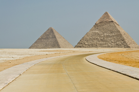 The concrete road turns to the Egyptian pyramids in the middle of barren desert under the blue sky