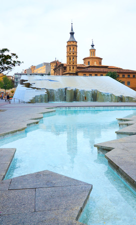 The fountain is photographed on the square del Pilar in Zaragoza  There is the church de San Juan de los Panetes behind  photo