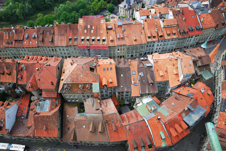 adjacent: Fribourg is photographed from above  Its old city is one of the best maintained in Switzerland  There are red tile roofs, dense building up, narrow streets, medieval townhouses tightly adjacent to each other  The molasse buildings are many storeys high  Stock Photo
