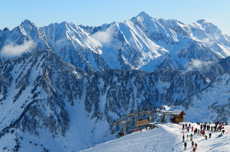 Winter Pyrenees is photographed at the Cauterets ski resort  Many skiers have been transported with Grand Barbat Chair lift up the snowy slope at the Cirque du Lys  There is range of mountains  Soum de Mauloc  in the background    Redakční