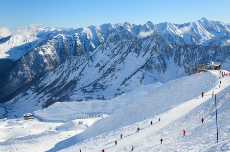 Skiers are sliding down snow-covered hill on skis at the Cirque du Lys  There is range of mountains  Soum de Mauloc  in the background  Winter Pyrenees is photographed at the Cauterets ski resort   photo