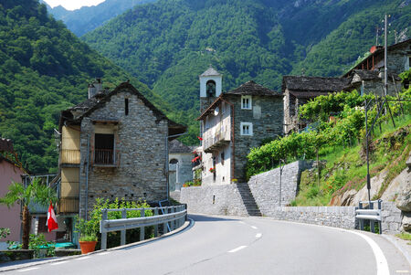 forested: Asphalt road is winding through picturesque Swiss village in the famous valley Verzasca  It is situated  in the middle of the forested mountains