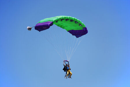 parachutists: Parachutists coupled with one parachute is flying in the blue sky