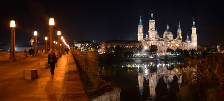 spotlit: Passerby are having a night walk in the Stone bridge  Puente de Piedra  across the river Ebro in Zaragoza  The spotlit cathedral  Basilica of Our Lady of the Pillar  is reflecting in water