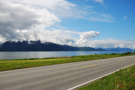 inclement weather: Asphalt road is running along the Norwegian coast  Highway is photographed with diminishing perspective  In the background there are blue fjord and dark cliff under the cloudy sky