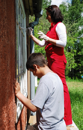 A young woman and a teenage boy are repairing house on the outside  She is staining with the brush  He is cleaning the old window   photo