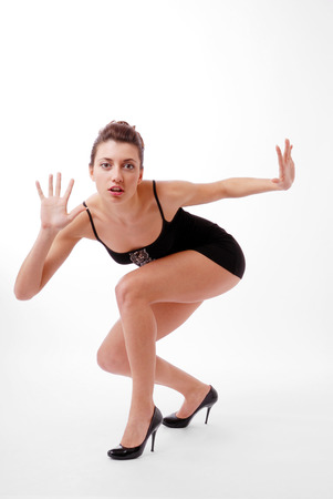 squatting down: Strained young woman is squatting down  Her hands are moved apart and fingers are spread wide  She is frightened  She is wearing a short black dress and pumps  Stock Photo