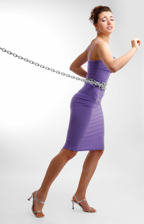 fetter: Pretty girl is shackled with steel chain around waist  She is towing heavy fetter  A close dress accentuates her slender body