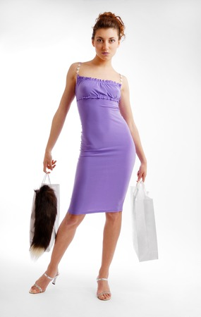 narrowly: Pretty girl is standing and holding packages  She is looking at the camera close  She is concentrated  Clinging lilac dress is accentuated slender body  Isolated on white  Stock Photo