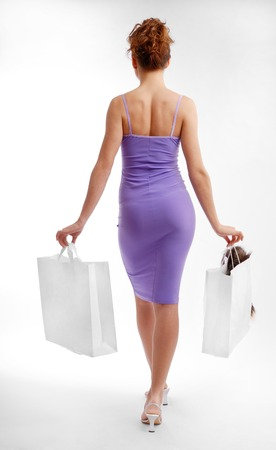 clinging: Pretty girl is going and carrying packages, rear view  Clinging lilac dress is accentuated slender body  Isolated on white
