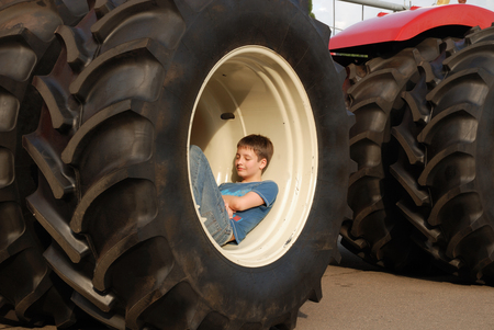 dozing: A pre-teen boy is dozing in the large wheel of the tractor