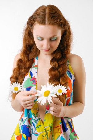 Youth woman is looking at a chamomile and plucking its petals  She is wearing a summer dress with bright floral pattern  She has two thick red plaits and three daisies  She is telling fortunes by the flower   Stock Photo