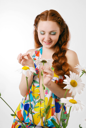 tell fortunes: Happy woman is speaking with a big chamomile and tearing its petals  She has two thick red plaits  She is telling fortunes by a flower  There are some daisies in the foreground