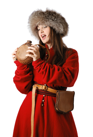 caftan: Young woman is wearing the vintage uniform of Tatar foot warrior of the 17th century  a red caftan and a fur-cap   She is going to drink into leather flask  She has bag on the belt  Stock Photo